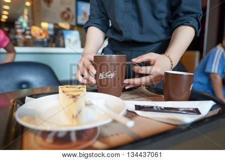SHENZHEN, CHINA - MAY 06, 2016: barista bring order at McCafe. McCafe is a coffee house style food and drink chain, owned by McDonald's.