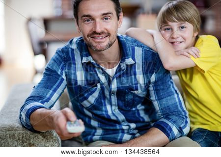 Father and son watching television in living room at home