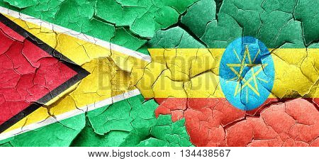 Guyana flag with Ethiopia flag on a grunge cracked wall