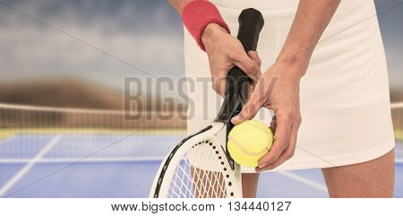 Athlete holding a tennis racquet ready to serve against facing view of net on tennis field