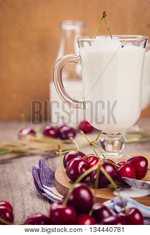 yogurt in two glass with ripe cherry and spica on wooden background