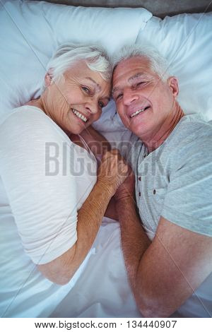 Portrait of happy senior couple holding hands while lying on bed in room
