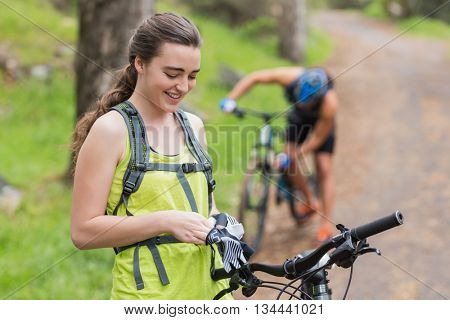 Happy young woman wearing gloves on footpath in forest