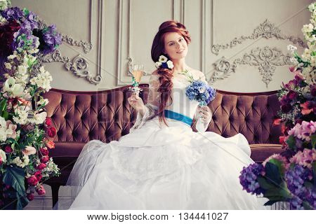 Beautiful bride in a luxurious interior with flowers