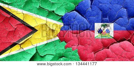 Guyana flag with Haiti flag on a grunge cracked wall
