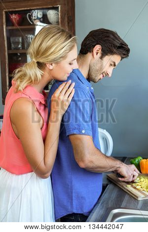 Young couple chopping vegetables in kitchen at home