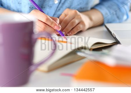 Female student or designer at workplace holding pencil and writing or making sketches. Woman writing letter list plan making notes doing homework. Education or creative work concept