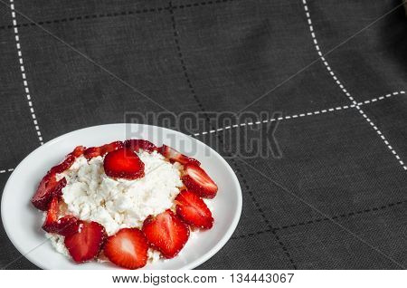 Slices strawberries is lying on delicious cottage cheese. Cottage cheese is lying on a plate with slices of strawberries.