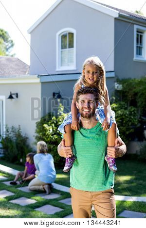 Portrait of smiling father carry daughter on shoulders in yard against house