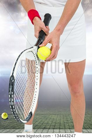 Athlete holding a tennis racquet ready to serve against american football arena