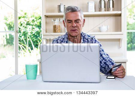 Senior man shopping online using laptop at kitchen