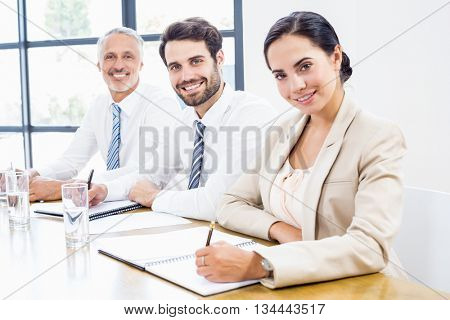 Portrait of business colleagues writing in diary during a meeting