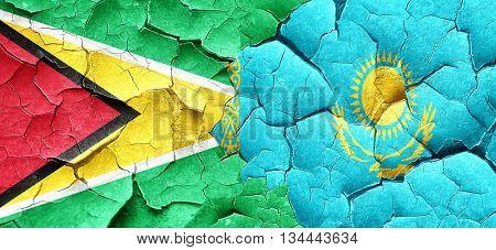 Guyana flag with Kazakhstan flag on a grunge cracked wall