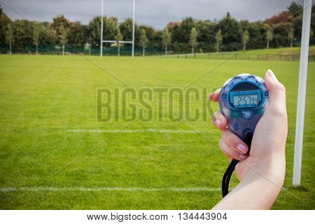 Close up of a hand holding a chronometer in a rugby pitch