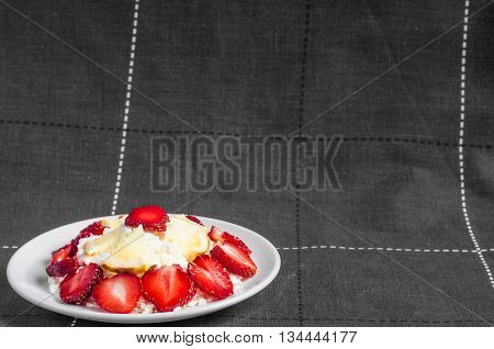 Sliced strawberries with lemon is lying on delicious cottage cheese. Cottage cheese is lying on a plate with slices of strawberries.