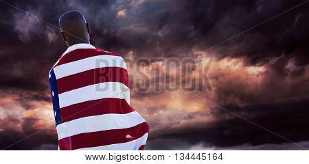 Rear view of man wearing american flag against gloomy sky