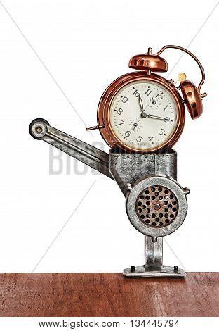 Bronze vintage alarm clock in meat grinder.Toned image.