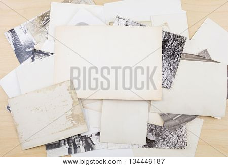Stack Of Old Photos On Wooden Surface.