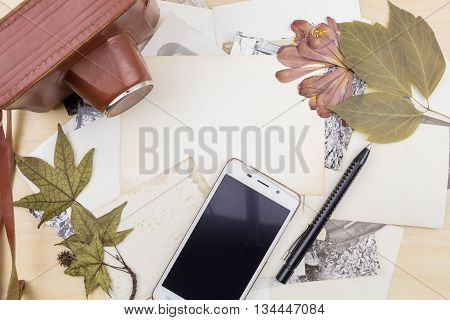 Old Camera And Smartphone On Stack Of Photos With Dry Plants, On Wooden Surface.