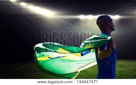 Profile view of sportsman holding a Brazilian flag against rugby stadium