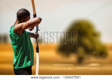 Rear view of sportsman doing archery on a white background against landscape of a field