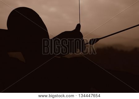 Close up of man stretching his bow against trees and mountain range against cloudscape