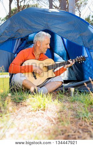 Mature man playing guitar on campsite
