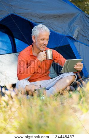 Mature man smiling and holding mug and tablet on campsite