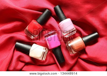 Colorful nail polish on red silk background