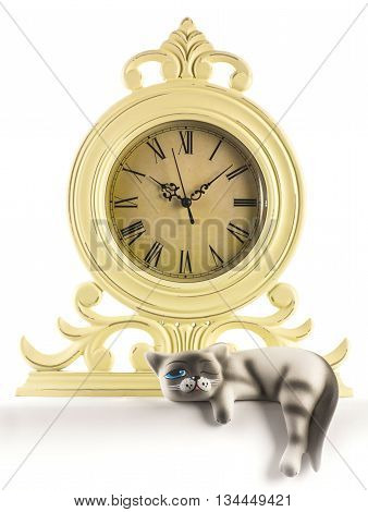 cat lies on a table at an antique clock on a white background