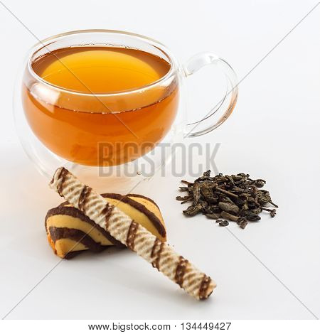 Double sided wall glass cup full of green tea with sweets biscuits and pile of dried leaves next to it against white background close up horizontal view