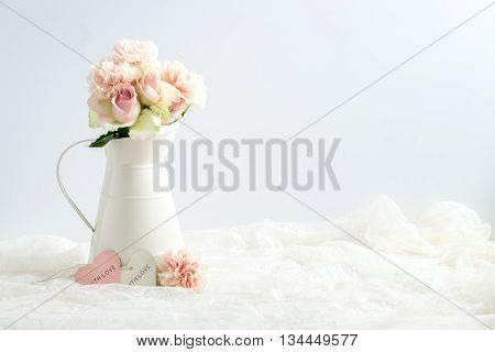 Mockup styled stock image of carnations and roses in a cream jug with a piece of lace. You can place your business promotion blog title quote headline or image in the space beside the jug.