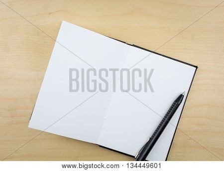 Open Notebook With Black Pen, On Wooden Surface.