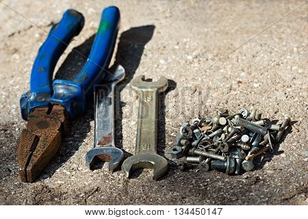 Old pliers, wrenches, screws on the concrete floor. A set of tools for installation and repair. Photo with selective focus, shot in candid light on a sunny day