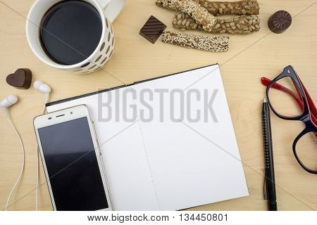 Opened Blank Notebook With Smartphone, Pen And Cup Of Coffee, On Wooden Desktop.