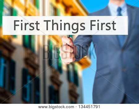 First Things First - Businessman Hand Holding Sign