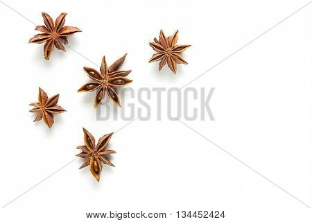 Star anise, scattered in a chaotic manner, isolated on white background