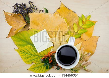 A Bouquet Of Yellow, Green Autumn Leaves, Cup Of Coffee And Blank Note