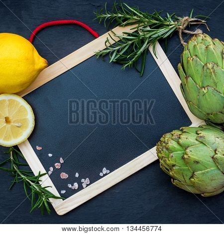 Organic fresh artichokes with lemon with copy space board, grunge background. Selective focus, top view