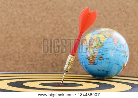 dart arrow hitting in target bullseye of center on dartboard with globe and wooden background with copy space business marketing financial and education success concept
