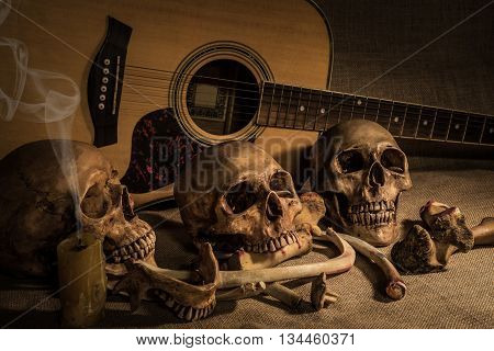 Still life painting photography with three skull and bones over guitar background horror halloween concept