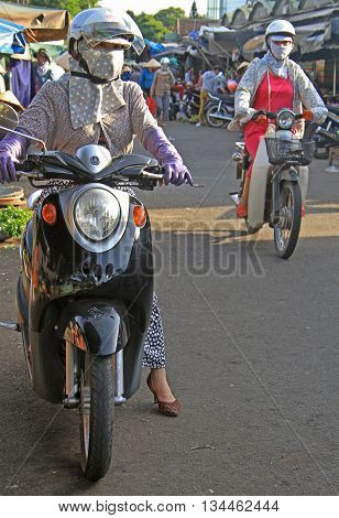 Hue Vietnam - May 27 2015: woman on scooter is waiting for someone on street market in Hue Vietnam