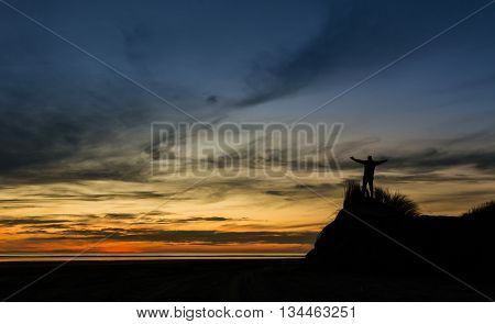 One man sanding on a sand hill with his hands up praising God for a wonderful sunset.