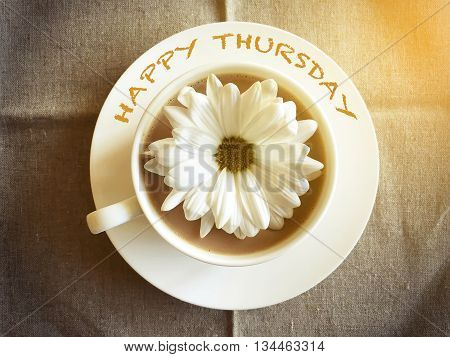 coffee cup on table with white daisy - Happy Thursday word vintage style