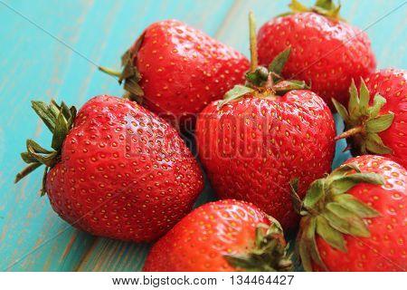 Strawberries on wooden blue desk. Stock photo.