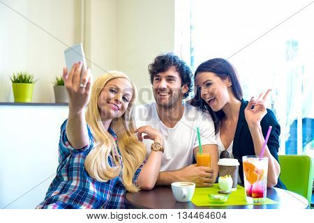 Friends siting at a table in a coffee shop and taking a selfie