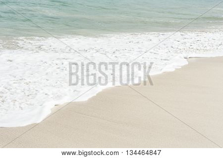 Wave gently glides up across a tropical white sand beach