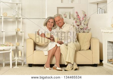 Two elderly people sitting on couch with tea