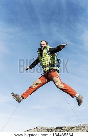man jumping with blue sky on mountains