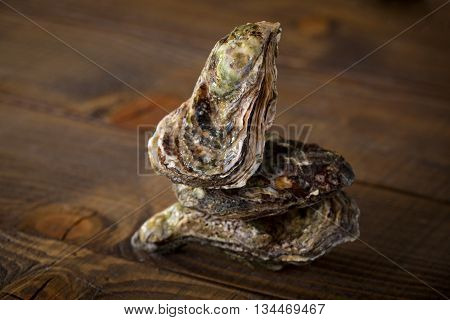 Raw oysters stacking on brown wooden background